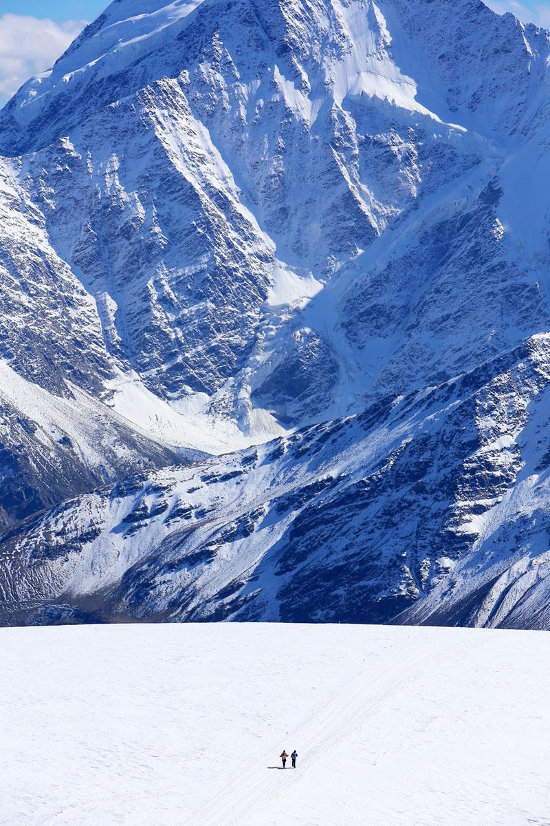 Восходители на Эльбрус спускаются с горы, на дальнем плане гора Донгузарун